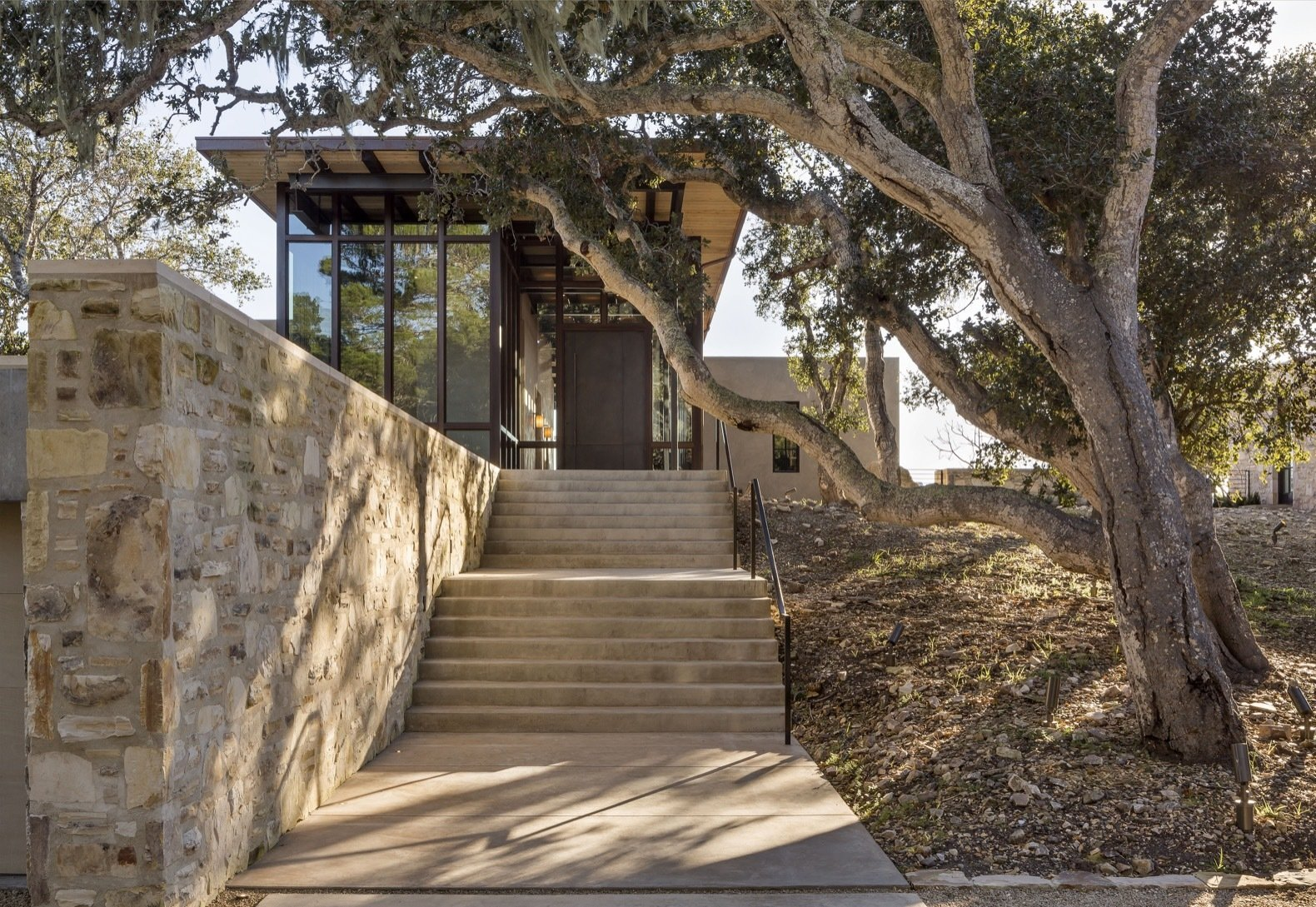 Exterior, Metal Siding Material, Concrete Siding Material, House Building Type, Flat RoofLine, and Glass Siding Material Stone walls, made with rock excavated on site, frame the ascent with cement steps.  Photos from Glass and Stone Combine to Dazzling Effect on California's Central Coast