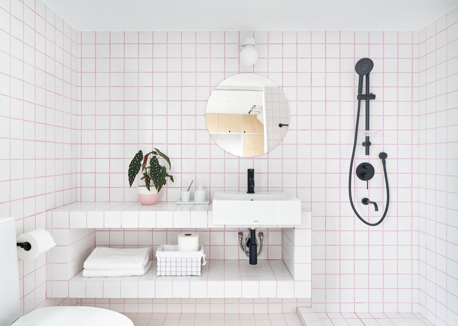 Bath Room, Ceramic Tile Floor, Vessel Sink, Tile Counter, Ceramic Tile Wall, Two Piece Toilet, Open Shower, and Wall Lighting The colored tile grout was sourced from Grout360. The tiles are from RAK Ceramics.    Best Photos from A Tiny Taipei Apartment Pursues Muji-Like Minimalism For $35K