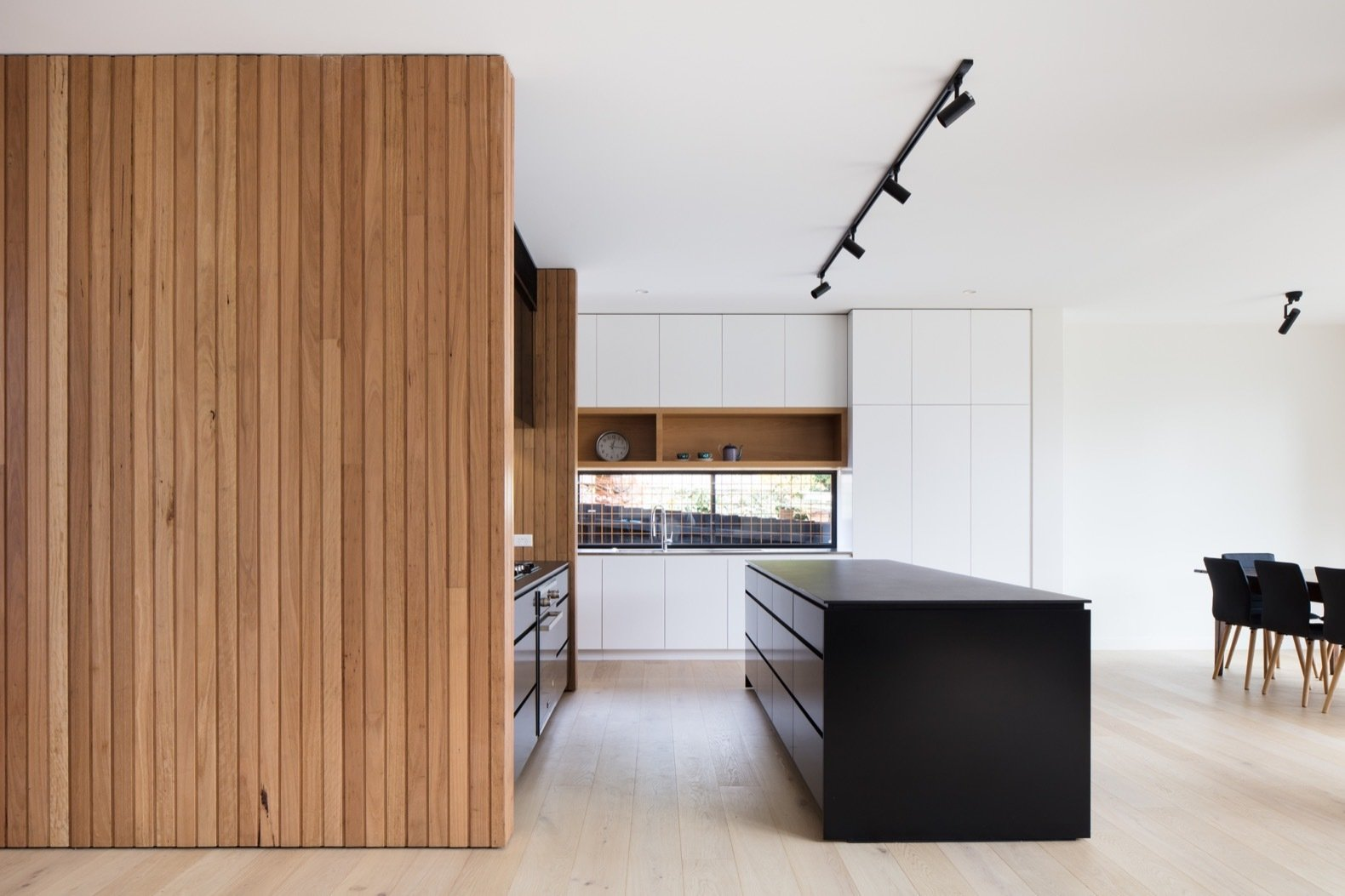 Kitchen, Ceramic Tile, White, Engineered Quartz, Wall Oven, Drop In, Cooktops, Track, and Light Hardwood The kitchen island is covered with a Dekton countertop.  Best Kitchen Ceramic Tile Light Hardwood Track Photos from A Melbourne Home Gains a Marvelous Modular Addition