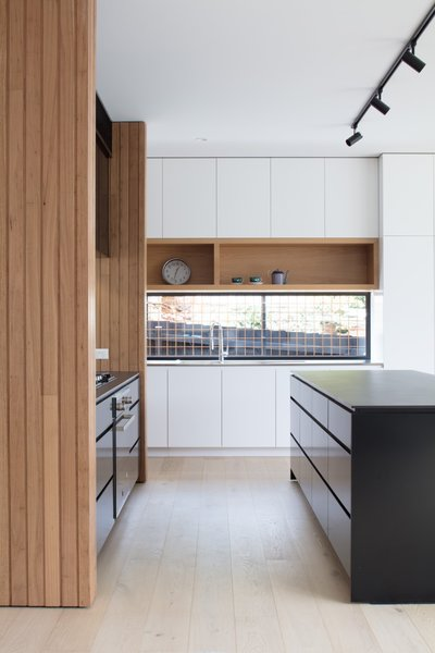 The white kitchen cabinetry is by Nikpol. The sink is integrated into a stainless steel benchtop.