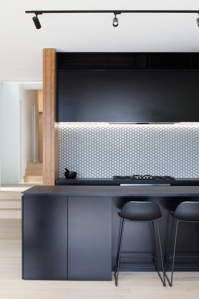 In this kitchen with matte black cabinets, elegant Perini Monroe ceramic tiles line the kitchen backsplash.