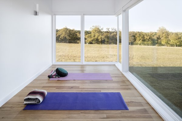The meditation room overlooks a nearby hilltop in one of the clients' favorite views, framed by floor-to-ceiling glass windows.