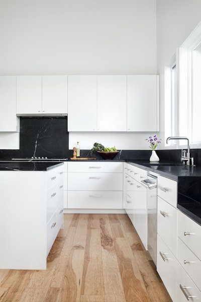 The kitchen is fitted with soapstone countertops and backsplashes from Architectural Tile & Stone, and white-painted custom cabinets from B Squared Woodworks.