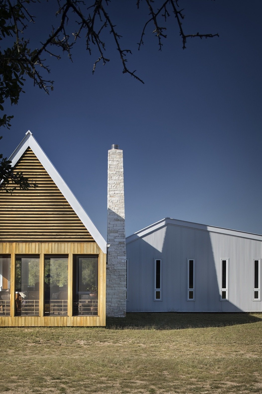Exterior, Wood, House, Metal, Metal, Gable, and Saltbox The tapered limestone chimney draws inspiration from an existing shed built of dry-stacked local stone.    Exterior Metal Saltbox Gable Photos from A Stellar Sustainable Home Is Built on a Surprisingly Low Budget