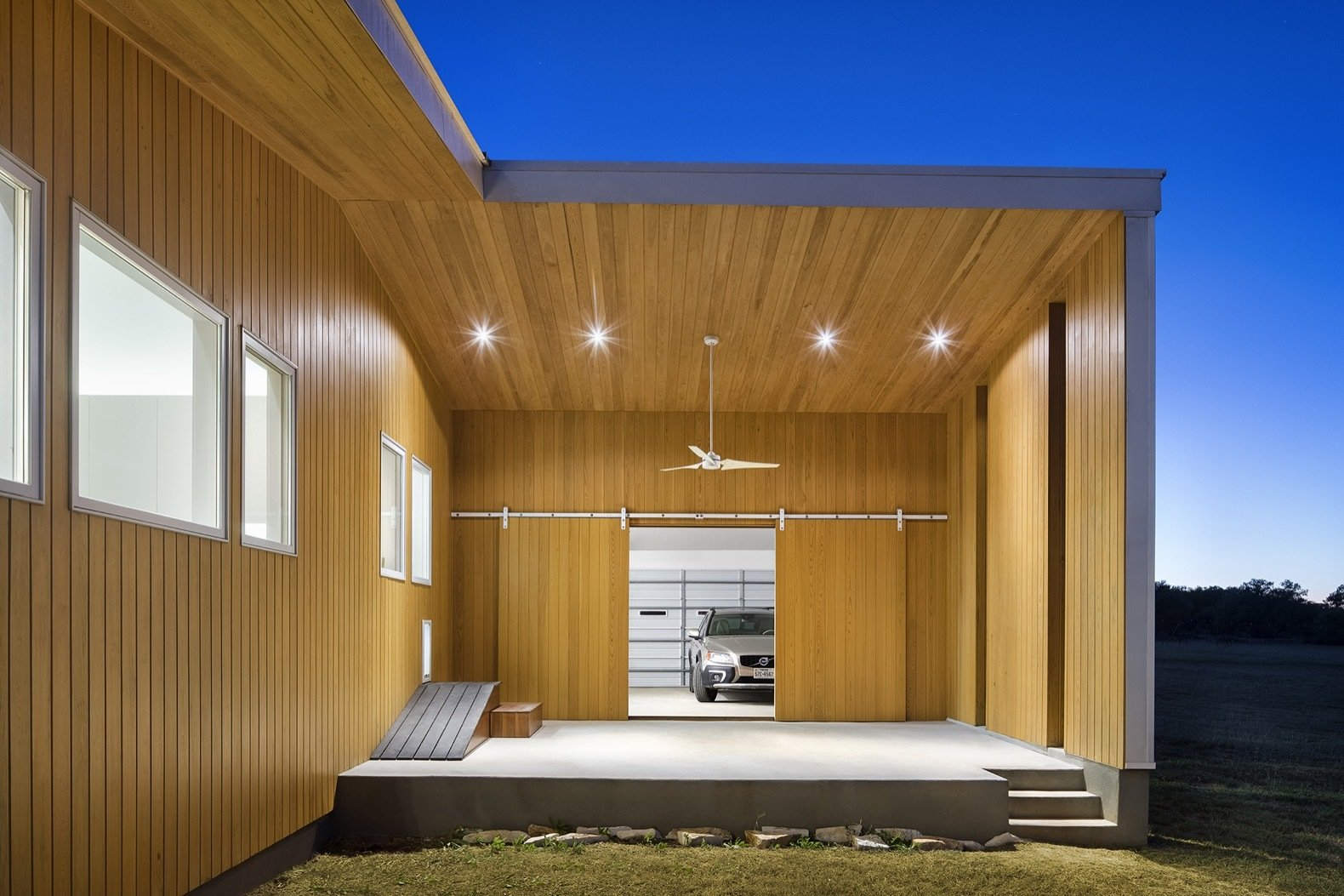 Garage and Attached Garage Sliding barn doors connect the garage to a shaded outdoor sculptural studio that doubles as a stage for summer concerts.    Best Garage Photos from A Stellar Sustainable Home Is Built on a Surprisingly Low Budget