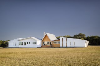"""""""Working within the restrictive budget, design was not sacrificed; rather, it inspired the team to find a vocabulary that was simple yet refined,"""" adds the firm. """"The exterior of the home is defined by clean lines, a sculptural gable roof, and a contrasting material palette of corrugated-aluminum and warm, locally sourced cypress. """""""