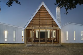 """""""The porch's distinctive 30-foot peak is discernible from a great distance, and its rhythmic, horizontal cypress slats are a contemporary interpretation of traditional vented gables,"""" add the architects."""