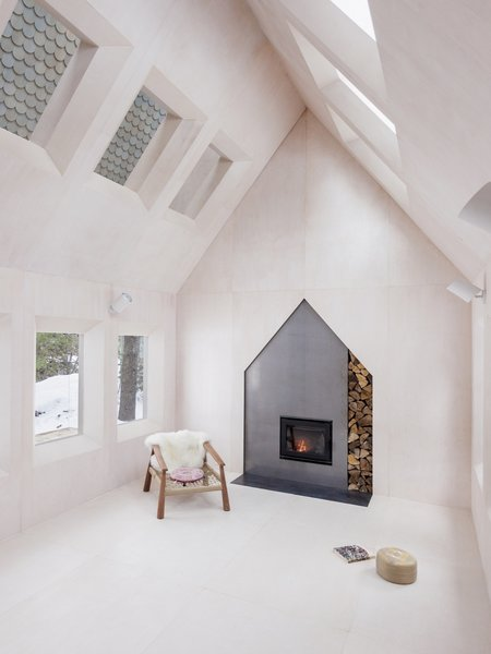 A wood-burning fireplace with a playful house-shaped surround anchors one end of the main living space.