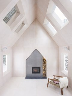 A total of 14 windows punctuate the living room, with half of them overlooking peripheral rooms to give the cabin a house-within-a-house feel.