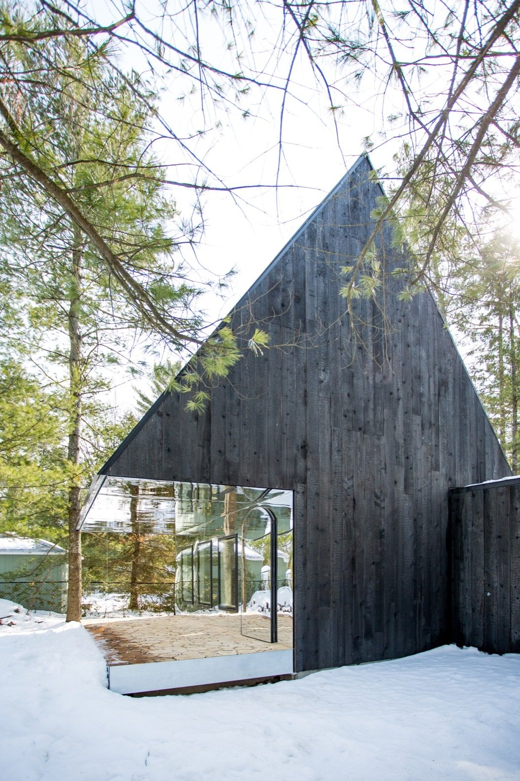 Outdoor, Trees, Wood, Woodland, and Small The outdoor terrace is oriented to face the lake.   Best Outdoor Small Woodland Photos from This Mirrored Cabin Playfully Brings a Forest Indoors