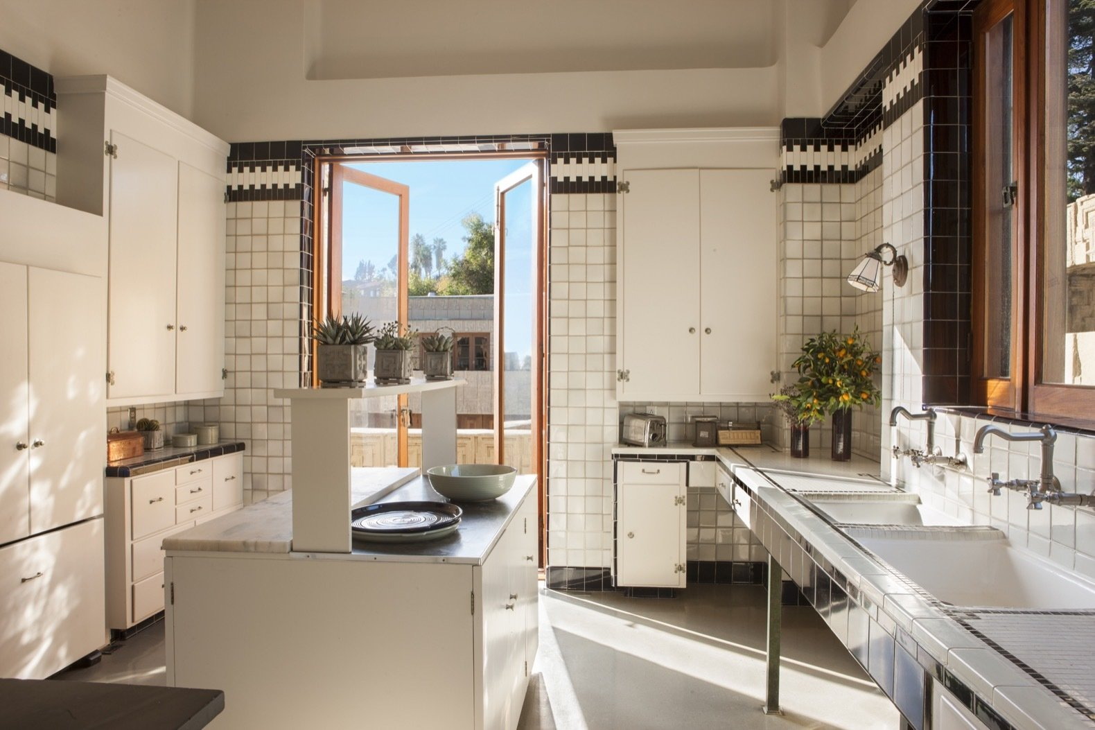 Kitchen, White Cabinet, Ceramic Tile Backsplashe, Wall Lighting, Marble Counter, and Undermount Sink Lovely tilework lines the restored kitchen.    Photo 21 of 23 in Frank Lloyd Wright's Iconic Ennis House Is Listed For $23M