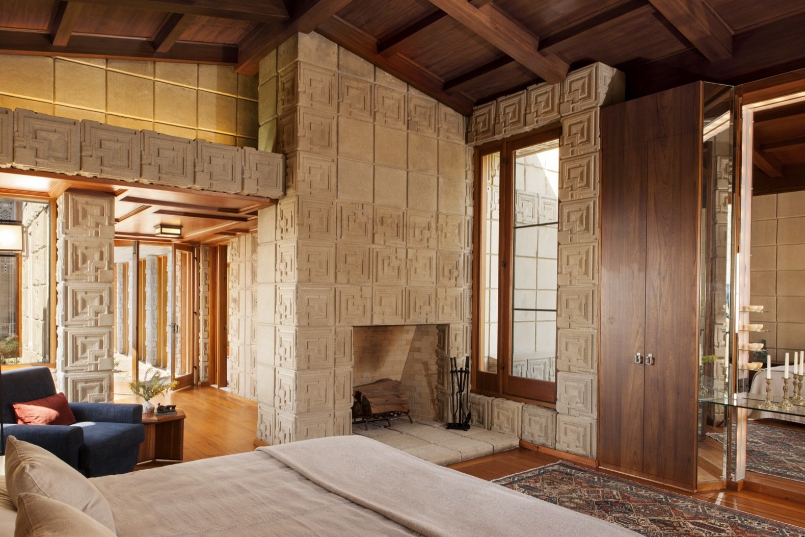 Bedroom, Bed, Medium Hardwood Floor, Chair, and Rug Floor The 6,200-square-foot property includes three bedrooms and three-and-a-half baths.  Photo 17 of 23 in Frank Lloyd Wright's Iconic Ennis House Is Listed For $23M