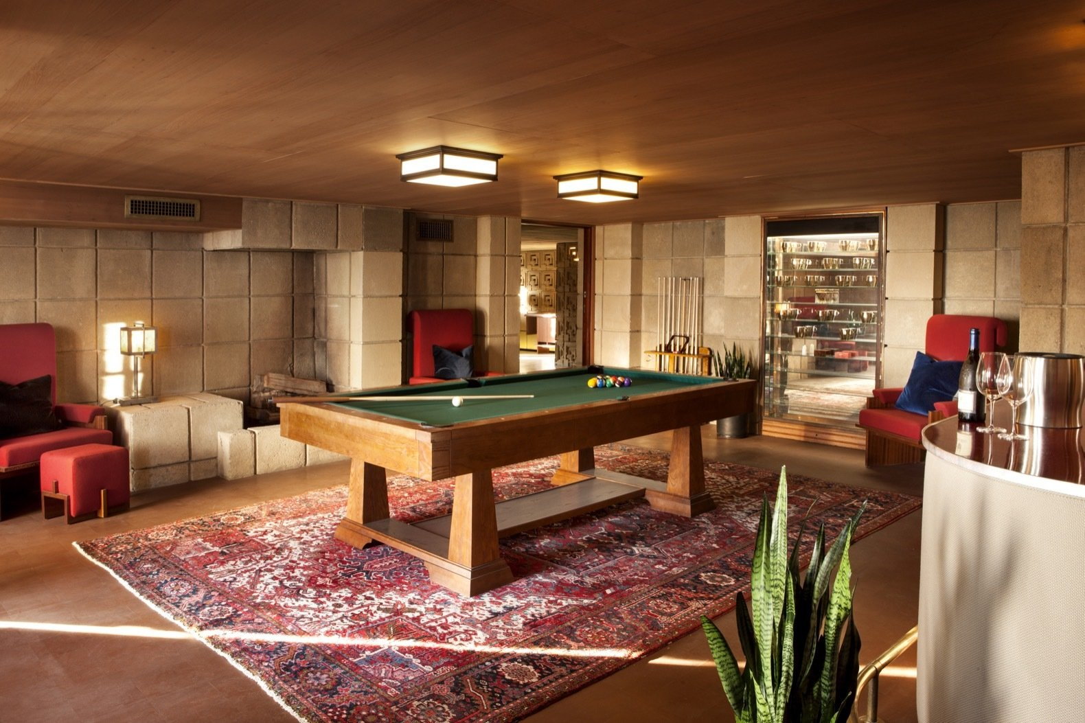 Living Room, Chair, Medium Hardwood Floor, Ceiling Lighting, Table Lighting, and Rug Floor After Nesbitt's purchase, Wright also converted the basement storage area into a billiard room.    Photo 23 of 23 in Frank Lloyd Wright's Iconic Ennis House Is Listed For $23M
