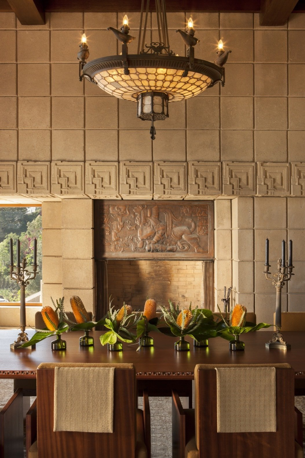 Dining Room, Chair, Medium Hardwood Floor, Table, Pendant Lighting, and Rug Floor Concrete blocks were also used to frame the interiors.   Photo 15 of 23 in Frank Lloyd Wright's Iconic Ennis House Is Listed For $23M