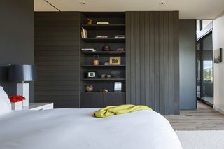 Floor-to-ceiling sliding panels divide the master bedroom from the living room. The sliding wall cladded in cedar is integrated into the casework, and hides the television when not in use.