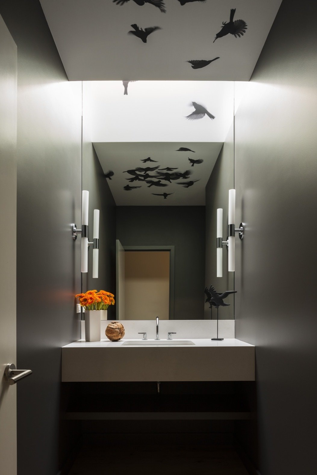 """Bath, Engineered Quartz, Medium Hardwood, Undermount, Accent, and Wall """"The owners have a love of blackbirds and had coveted this Indi wallpaper from Trove for years,"""" add the architects. """"The design team came up with the idea of applying it to the ceiling and wrapping it into the continuous skylight so the illusion of birds flying through could come to life. All who enter the room are surprised by the birds reflected in the mirror.""""    Best Bath Undermount Accent Wall Photos from A High Desert Home Slides Open Like a Swiss Army Knife"""