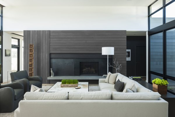 The fireplace wall features custom-fabricated blackened steel with a sliding panel that can conceal the television when not in use.