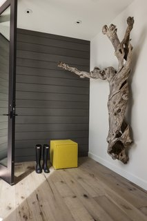 A sculptural lilac trunk—which is over a hundred years old—hangs on the entry wall and serves as inspiration for the interior color palette.