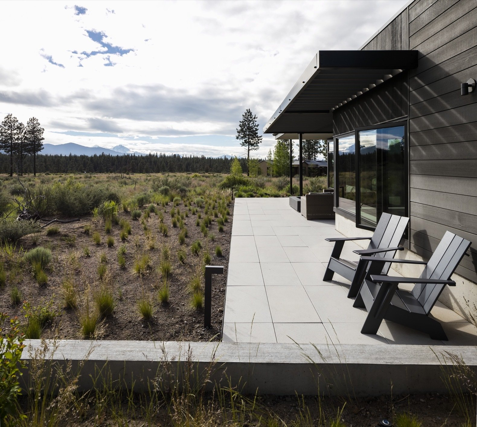 Outdoor, Back Yard, Shrubs, Concrete, Large, Trees, Grass, and Landscape Aluminum-framed sliding doors connect the living room to an outdoor patio.   Best Outdoor Landscape Photos from A High Desert Home Slides Open Like a Swiss Army Knife