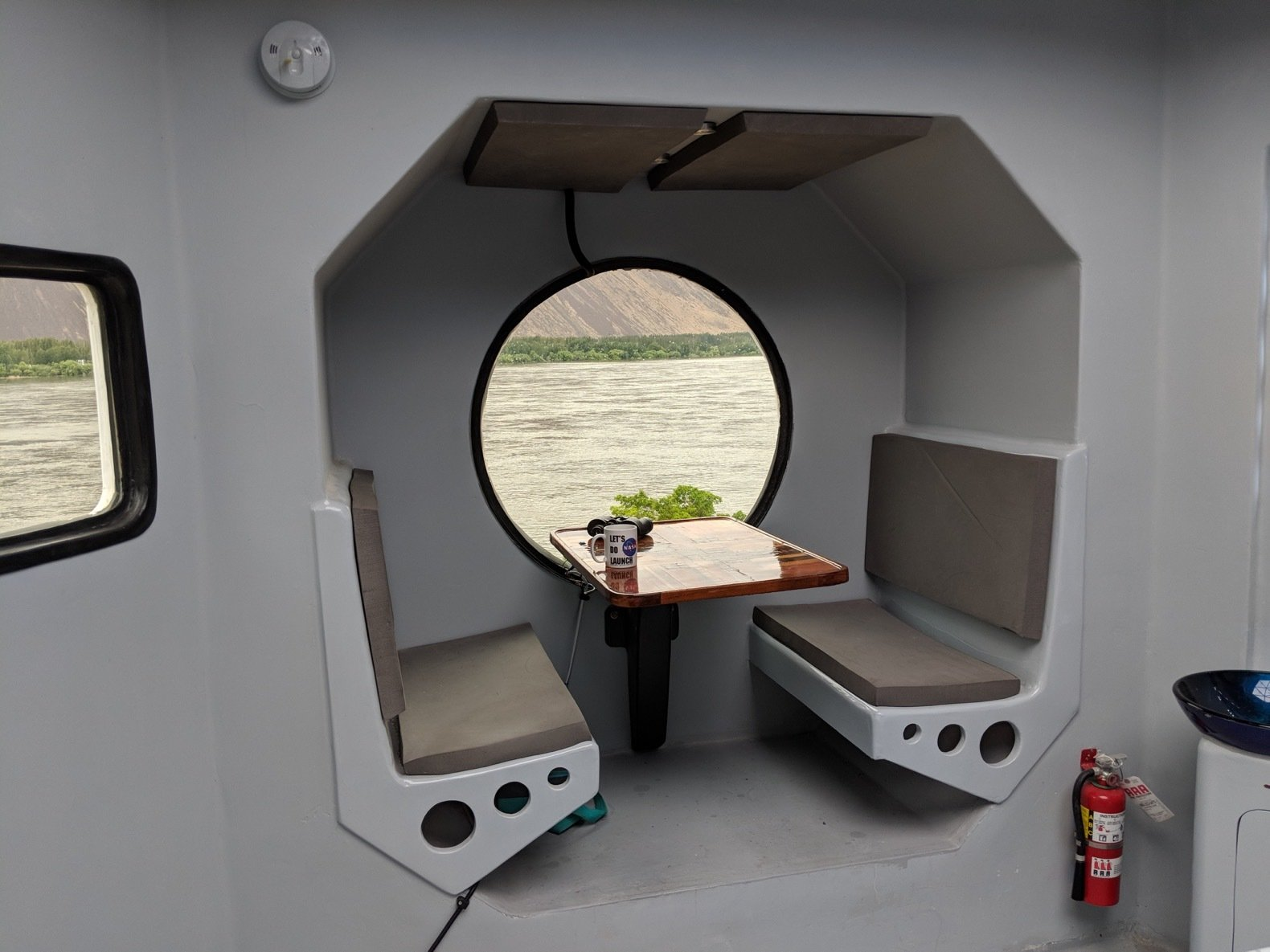Dining Room, Ceiling Lighting, Table, and Bench A look at the breakfast nook. The Lunar Lander can comfortably entertain up to four people.   Photos from A Lunar Lander-Inspired Tiny House is an Otherworldly Escape
