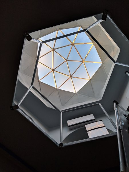A clear geodesic dome tops the structure, and floods the interior with natural light.