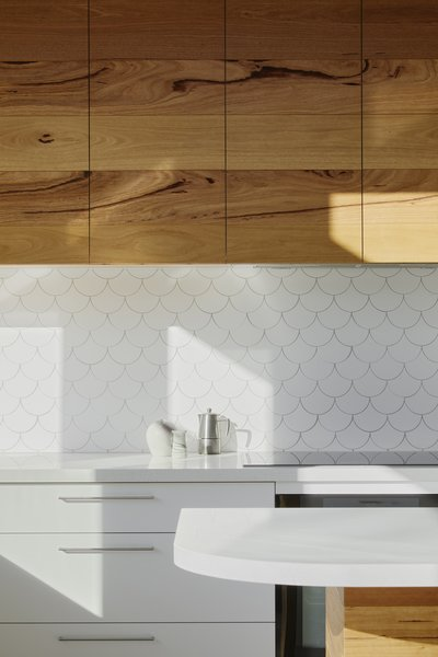 The kitchen's overhead cabinets have been built from solid timber recycled from re-milled Messmate hardwood floorboards. The dainty scallop tiles cover the kitchen backsplash, giving the space a visual identity.