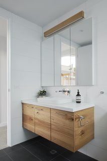 Caesarstone countertops (Ocean Foam) in the bathroom complement the tiled walls and flooring.