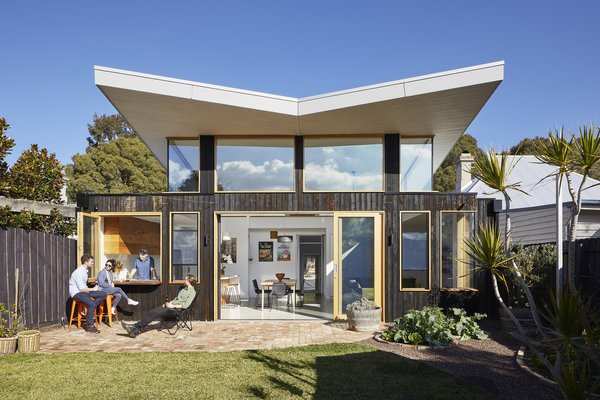 This eco-friendly extension in Melbourne was designed by Ben Callery Architects. The light-filled space incorporates renewable features including high levels of insulation, double glazing, and recycled and locally sourced materials. A corrugated metal roof was designed to glide over the 1,650-square-foot home.