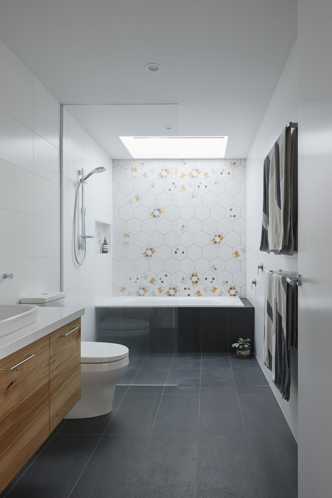 Bath, Engineered Quartz, Two Piece, Porcelain Tile, Recessed, Vessel, Open, and Alcove A strategically placed skylight bathes the shower area in natural light.  Best Bath Two Piece Recessed Photos from An Uplifting Melbourne Addition Embodies its Owners' Sense of Adventure