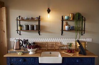 A white, hexagonal tile backsplash adds a modern touch to the upcycled 19th-century oak sideboard.