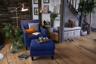 A Rotterdam Club Chair and Ottoman anchor this cozy corner of the living space, while an exposed timber wall and pockets of greenery bring the outdoors in.
