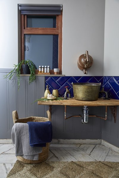 Bath Room, Vessel Sink, Wood Counter, Painted Wood Floor, and Rug Floor An old brass jam pan has been repurposed into the bathroom sink, while the tap is a reclaimed French copper kettle.  Ravendere Retreats from A Luxe, Handcrafted Tree House Offers Blissful Escape Into Nature