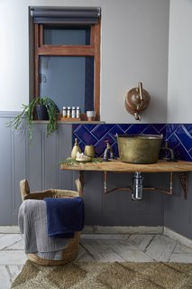 An old brass jam pan has been repurposed into the bathroom sink, while the tap is a reclaimed French copper kettle.