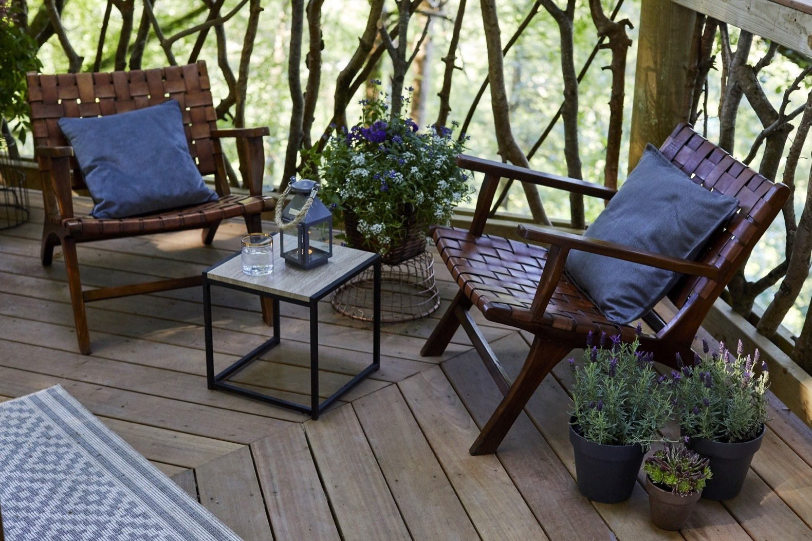 Outdoor, Trees, Woodland, Wood Fences, Wall, and Large Patio, Porch, Deck Surrey Garden Chairs offer the perfect place to lounge amidst the tree canopy.  Ravendere Retreats from A Luxe, Handcrafted Tree House Offers Blissful Escape Into Nature