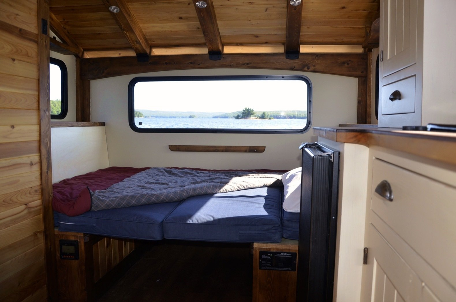 Bedroom, Bed, Recessed Lighting, Medium Hardwood Floor, and Storage The dinette transforms into a sleeping area once the table is lowered and the cushions are folded out. The benches include hidden storage.  Photo 4 of 15 in Kick Back in This Tiny, Solar-Powered Houseboat For $61K