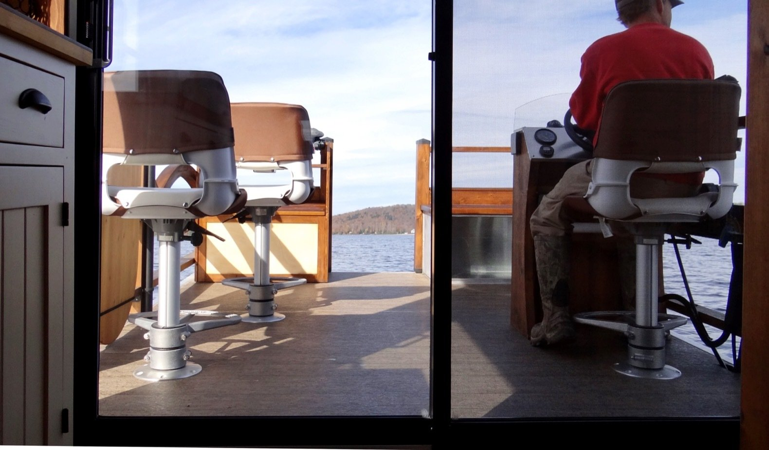 Outdoor, Wood Patio, Porch, Deck, and Small Patio, Porch, Deck The patio is equipped with three Springfield swivel chairs with footrests.  Photo 7 of 15 in Kick Back in This Tiny, Solar-Powered Houseboat For $61K