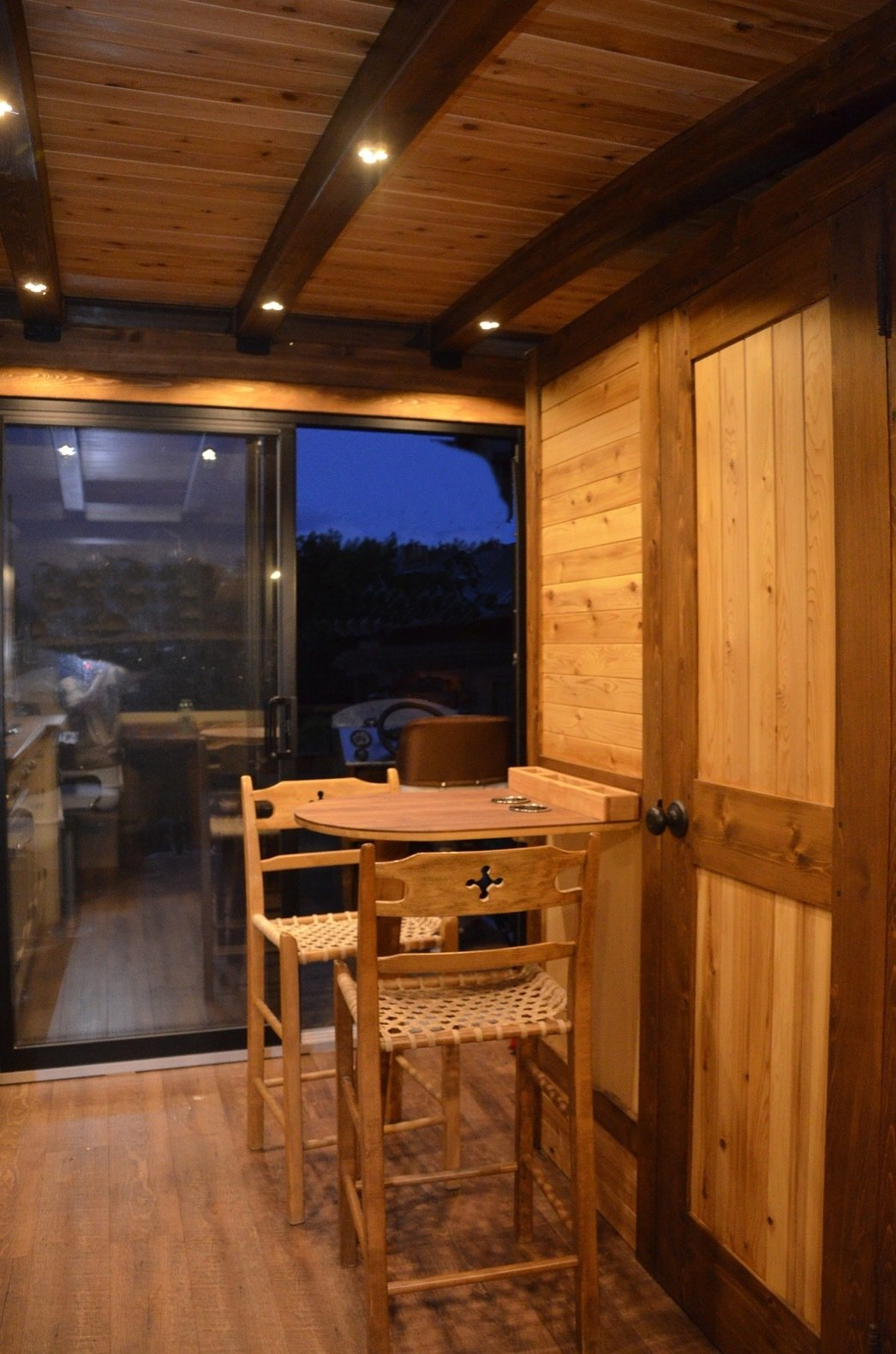 Living Room, Medium Hardwood Floor, Chair, Table, and Recessed Lighting A 24-inch bistro table juts out from the bathroom module.  Photo 6 of 15 in Kick Back in This Tiny, Solar-Powered Houseboat For $61K