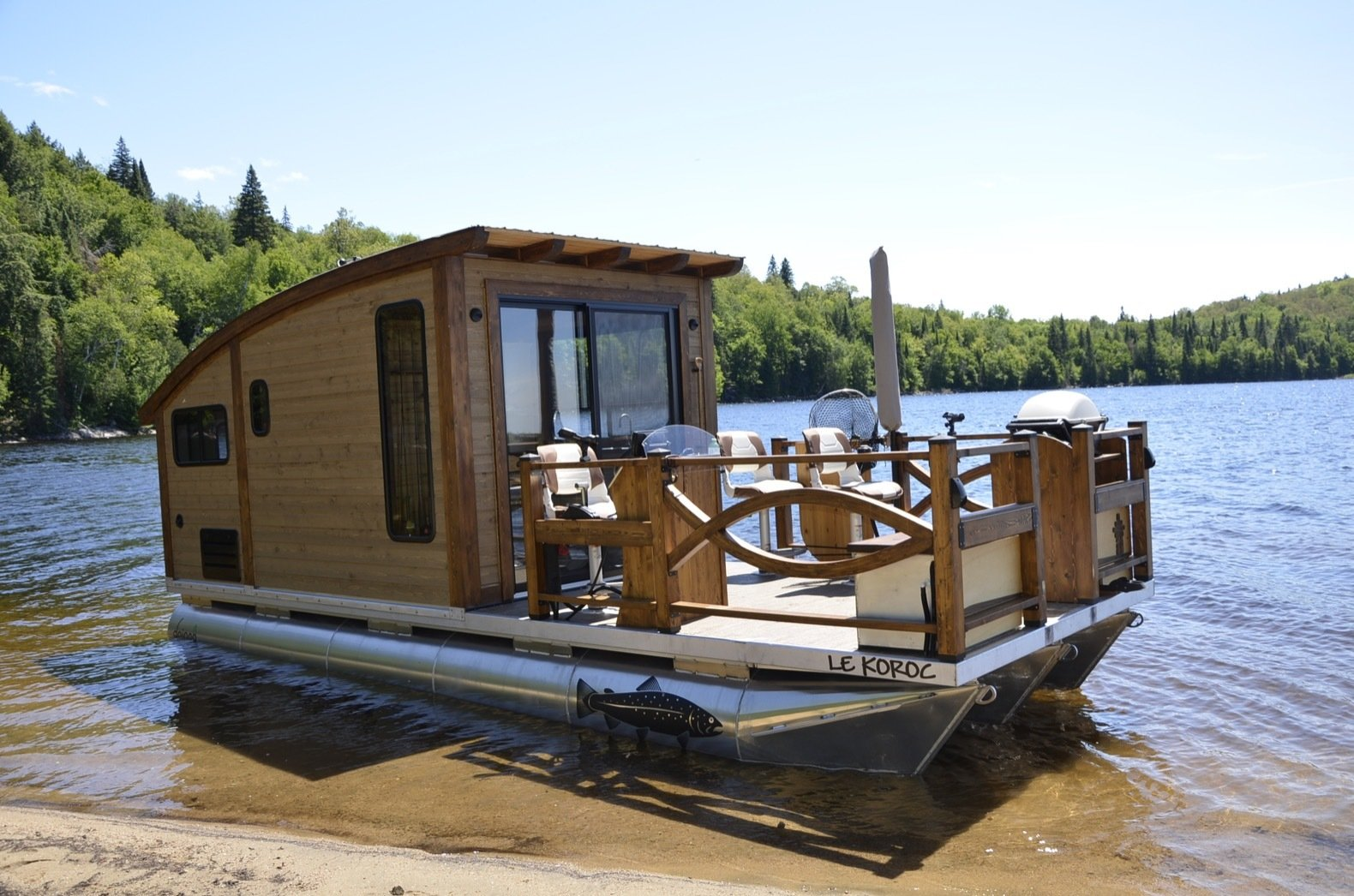 Exterior, Wood Siding Material, Boathouse Building Type, and Curved RoofLine Sliding glass doors connect the cabin with a spacious patio.   Photo 1 of 15 in Kick Back in This Tiny, Solar-Powered Houseboat For $61K