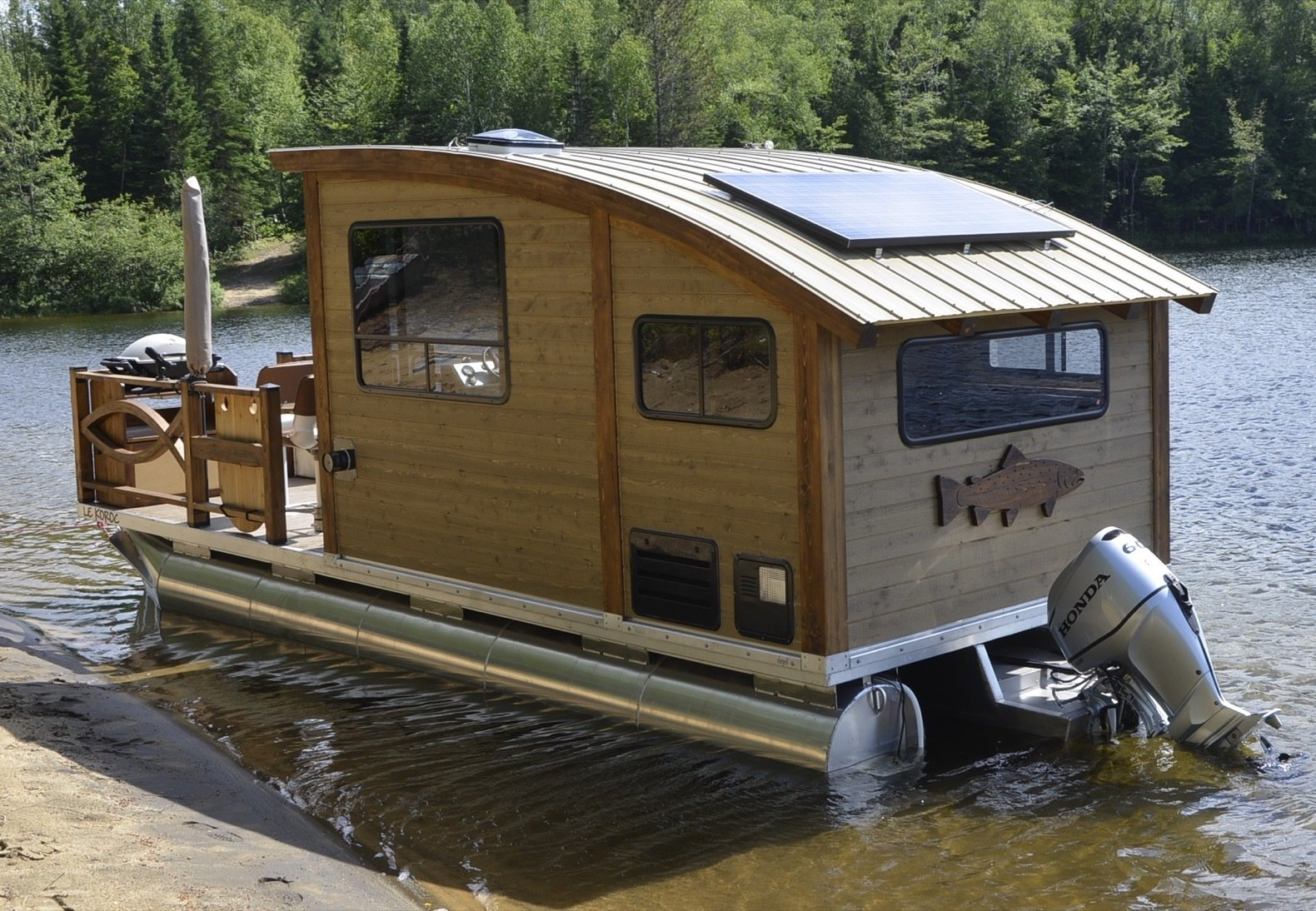 Exterior, Curved RoofLine, Wood Siding Material, and Boathouse Building Type Le Koroc is equipped with a Honda BF90 VTEC outboard motor with 25-inch-long shaft (and a marine battery) as well as a 192-liter gas tank. A 265-watt solar panel with two serial 6-volt batteries provides all of the unit's electricity needs.  Photo 2 of 15 in Kick Back in This Tiny, Solar-Powered Houseboat For $61K