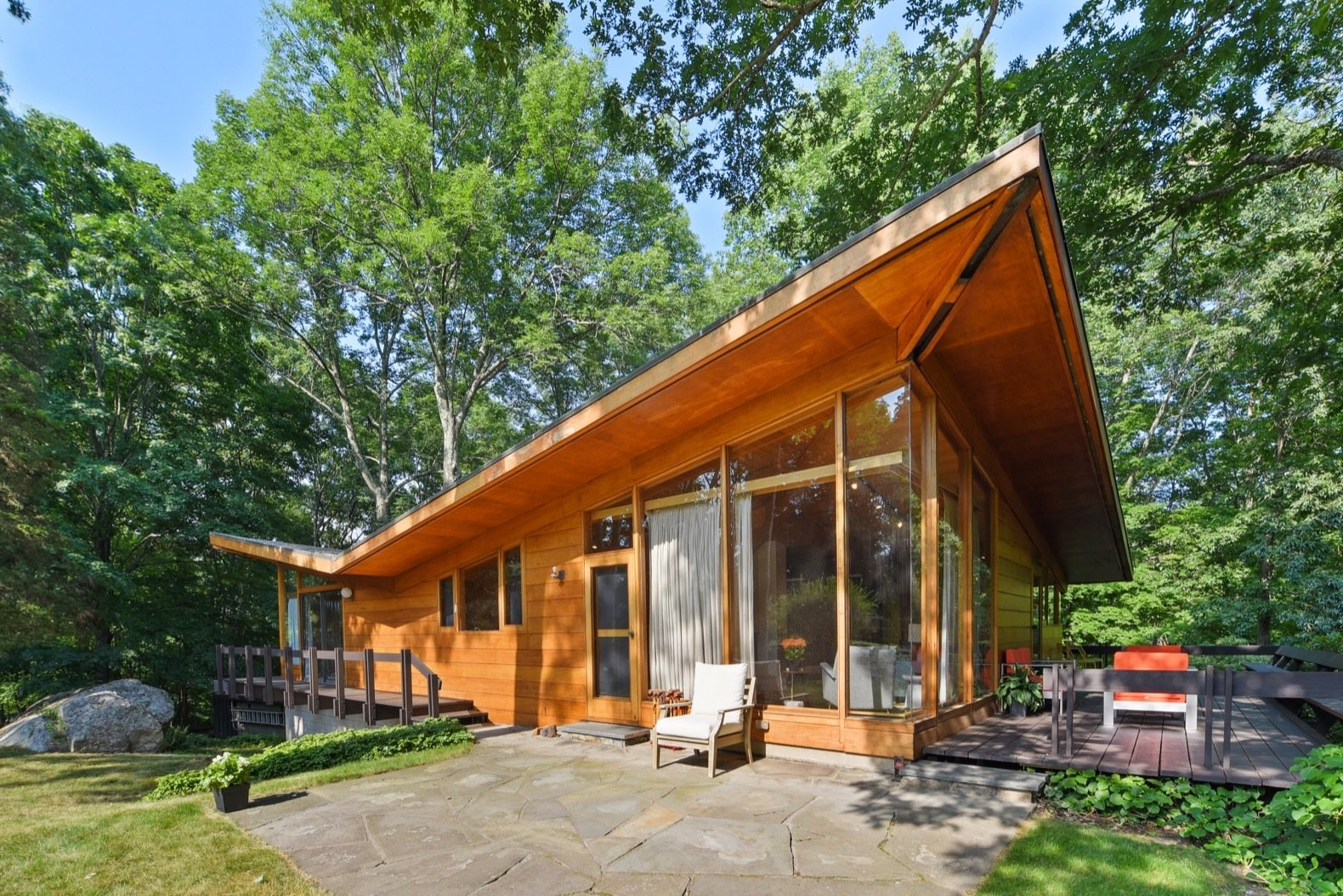 Exterior, House, Mid-Century, Wood, and Butterfly Overhanging roof eaves help protect the home from unwanted solar gain.  Best Exterior Butterfly Wood Photos from Moby's Luminous Midcentury in New York Asks $1.3M
