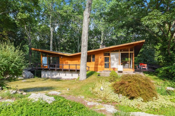 Once owned by musician, producer, and DJ Moby, this midcentury dwelling in Pound Ridge, New York, was restored to preserve its original architectural elements by David Henken, a disciple of Frank Lloyd Wright. Built in 1956, the two-story home was originally created by renowned local builder Vito Fosella to embrace the wooded landscape with an exterior clad in teak, mahogany, and stone. The roof is tar and gravel.