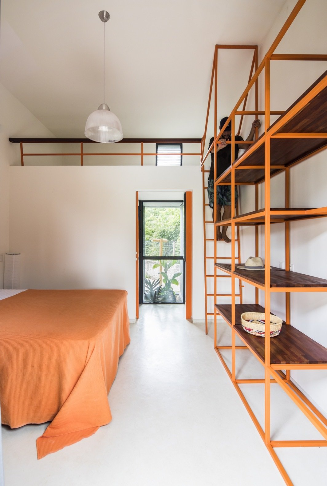 Bedroom, Bed, Concrete Floor, Storage, and Pendant Lighting The Bamboo House features three bedrooms to accommodate the clients' sons when they visit.  Photos from This Budget-Conscious Bamboo House Is a Slice of Paradise