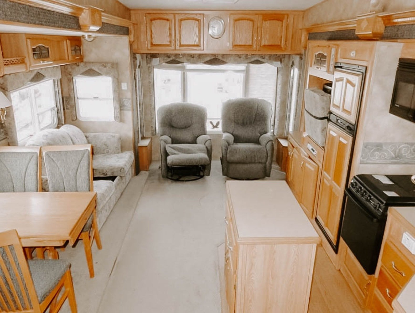 The wood paneling and dark colors made the living space feel small and cramped.    Photo 2 of 25 in Before & After: An Uninspired RV Gets a Cheery Refresh For $5K