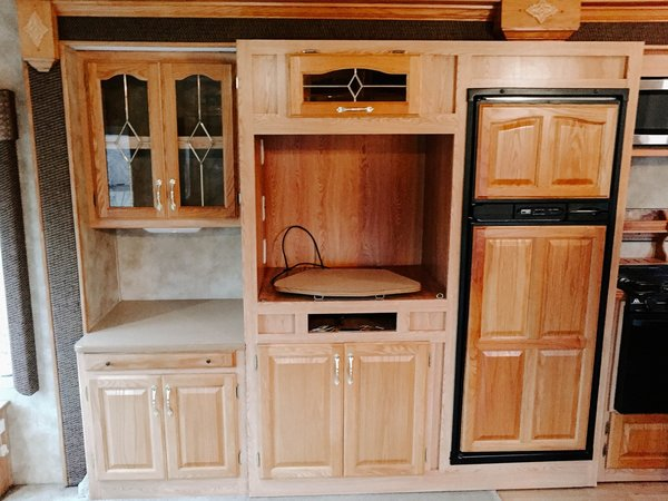 Because many of the cabinets were various sizes, the entertainment center felt extremely cluttered, even when it was empty.    Photo 11 of 25 in Before & After: An Uninspired RV Gets a Cheery Refresh For $5K