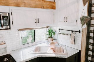 The upper cabinets were repainted with Rustoleum White Chalk paint, while new stick-on subway tile (from Tic Tac Tile) was applied to the backsplash.