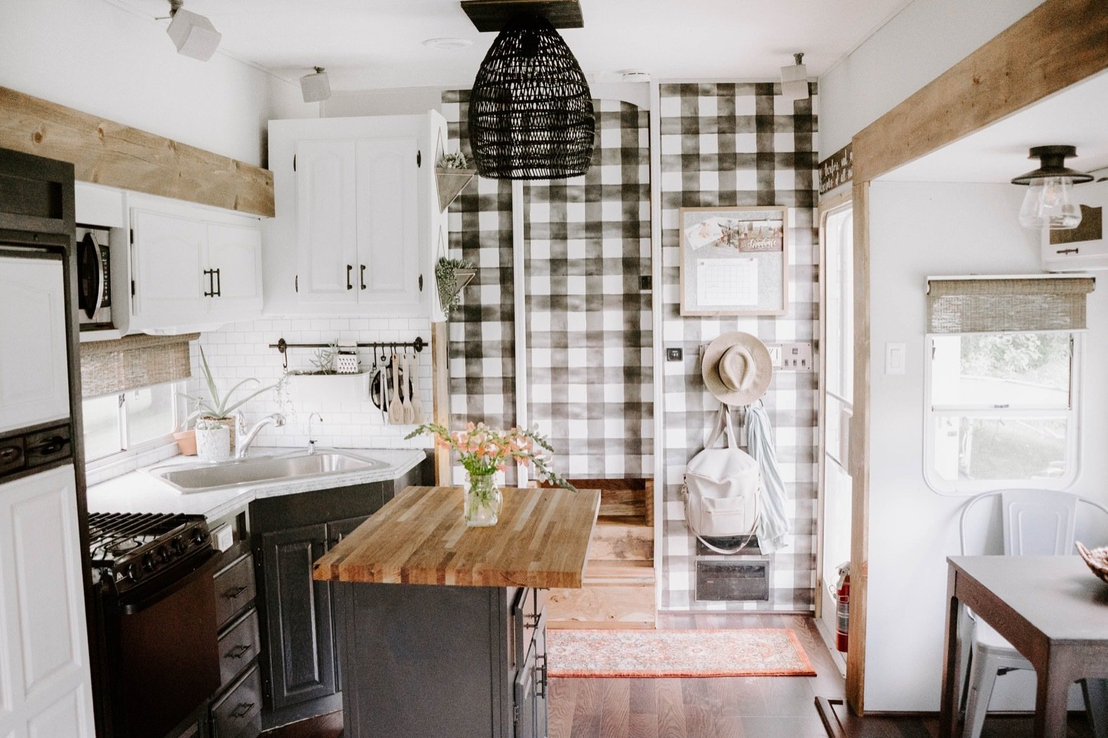 Kitchen, Medium Hardwood Floor, Microwave, Subway Tile Backsplashe, Refrigerator, White Cabinet, Drop In Sink, Wood Counter, Ceiling Lighting, and Range The couple didn't cover all the walls with paint. Instead, they applied Buffalo plaid wallpaper (from Home Depot) to select areas.    Photo 10 of 25 in Before & After: An Uninspired RV Gets a Cheery Refresh For $5K