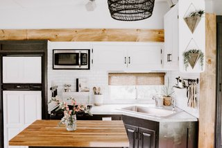 The kitchen counter was repainted with Giani Faux Granite paint and the lower cabinets were repainted with Sherman Williams Iron Ore.  A new butcher-block now tops the kitchen island.