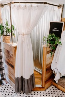 The creative duo tore out the glass shower and inserted a new surround built of wood (the same used in the entertainment center) and corrugated roof tin. The shower curtain is from Anthropologie.