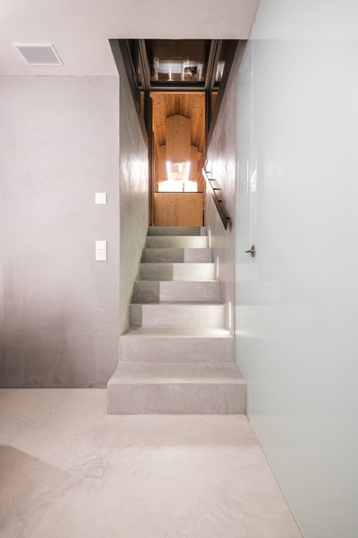 The concrete staircase that leads to the basement is illuminated with LED strips.