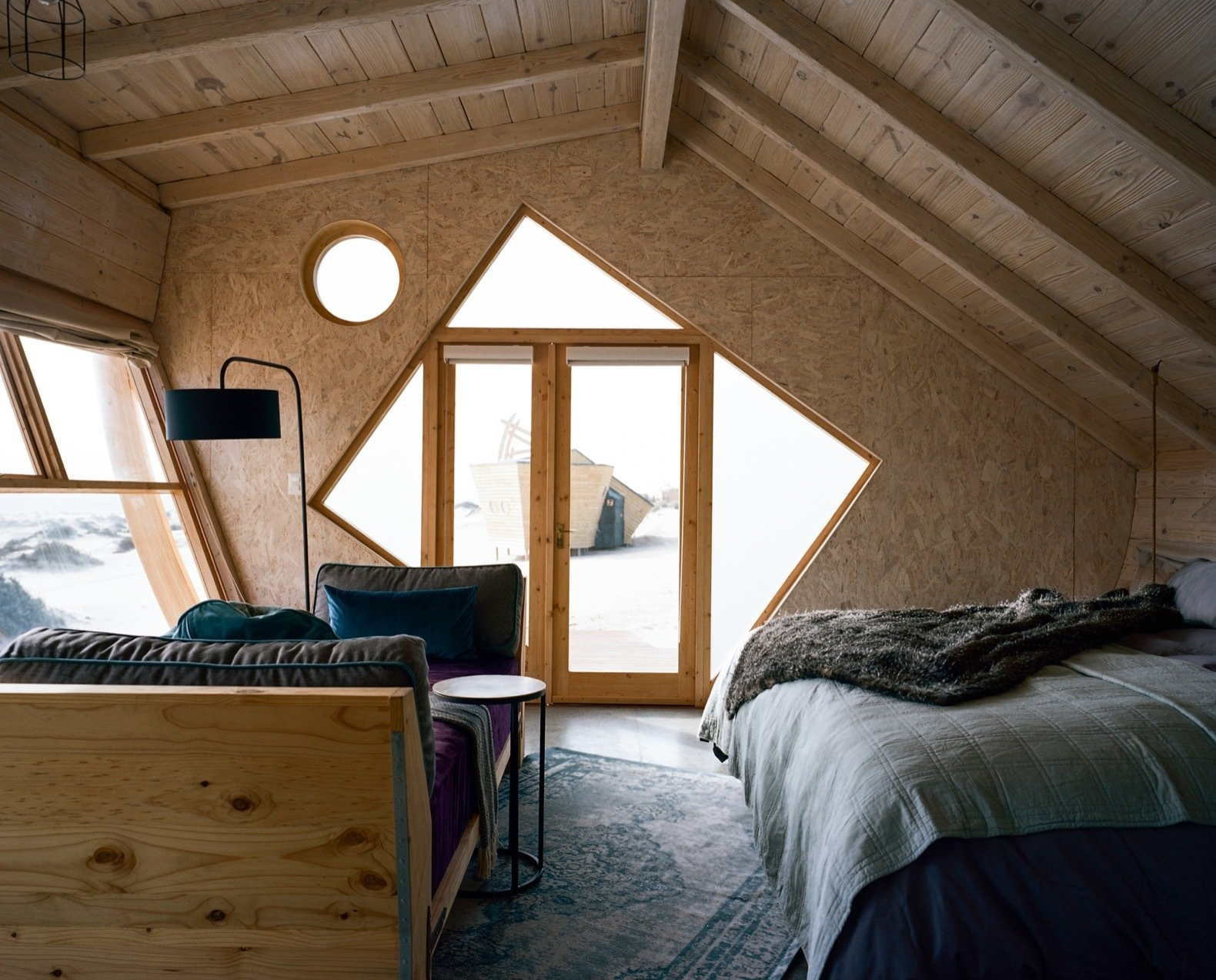 Bedroom, Floor, Bed, Pendant, and Rug The asymmetrical shape and tilted lines reinforce the impression that the cabins are capsized ships.   Best Bedroom Medium Hardwood Floor Photos from Explore Namibia's Haunting Coast With These Luxe Prefab Cabins